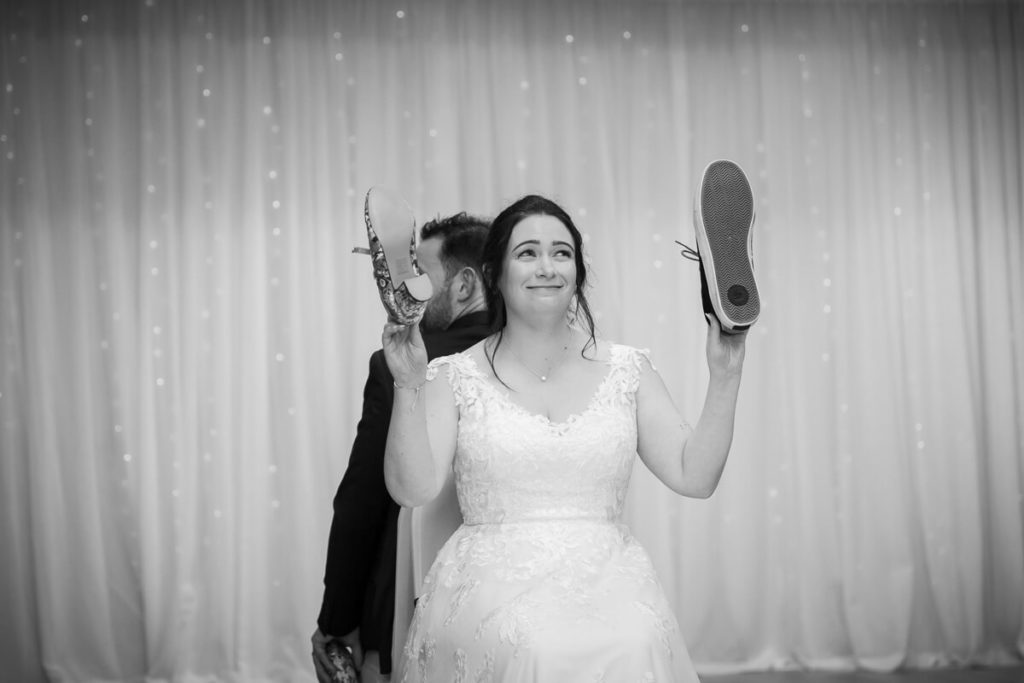 black and white image of a bride reacting to a questions whiel playing the weddig she game holding up one of her shes and also one of her new husbands