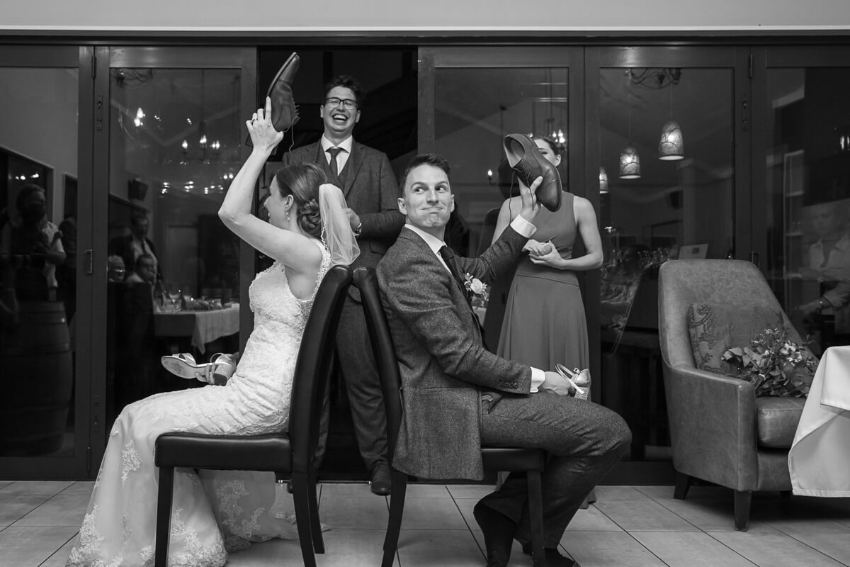 blakc and white image of a bride and groom playing the wedding she game with the MC in the background
