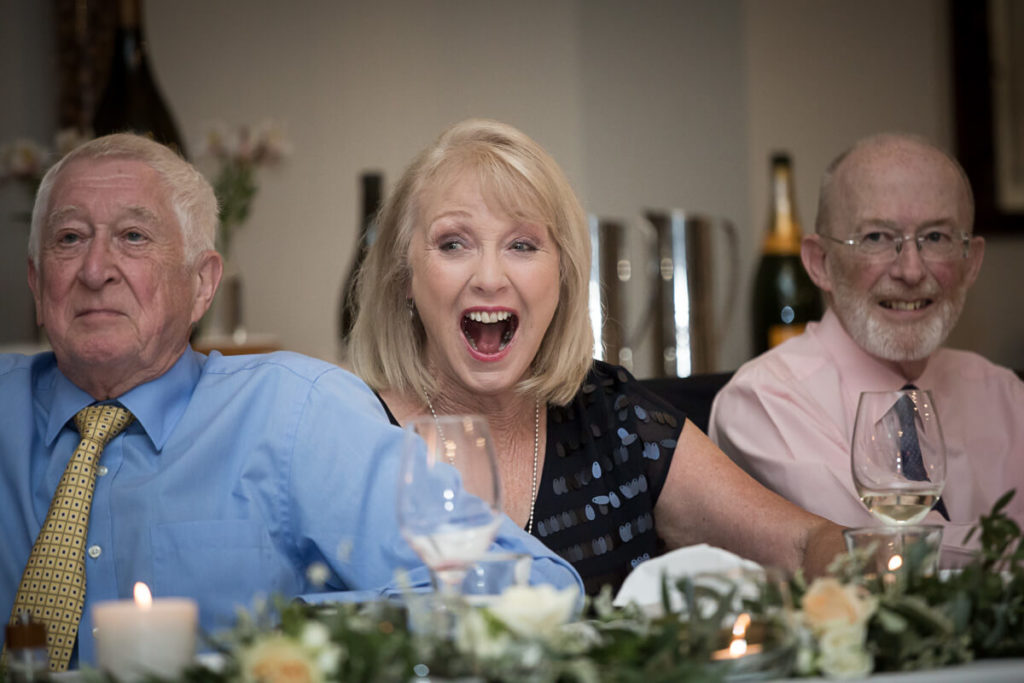 wedding guest reacting to somthing funny at the reception