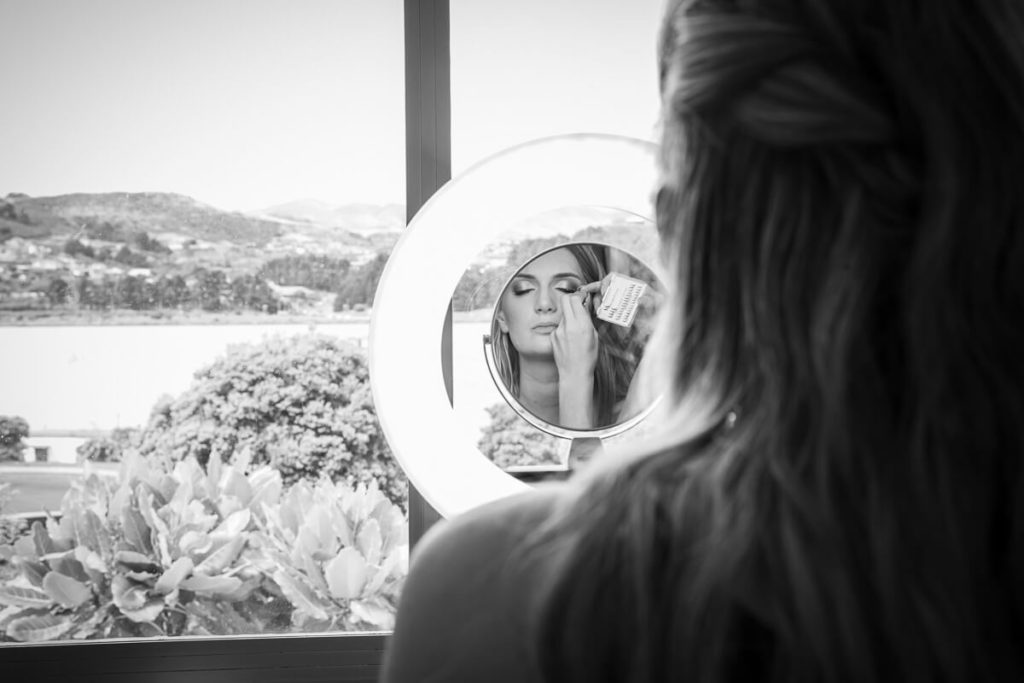 Bride having her make-up done before a round mirror with porirua harbor in the background