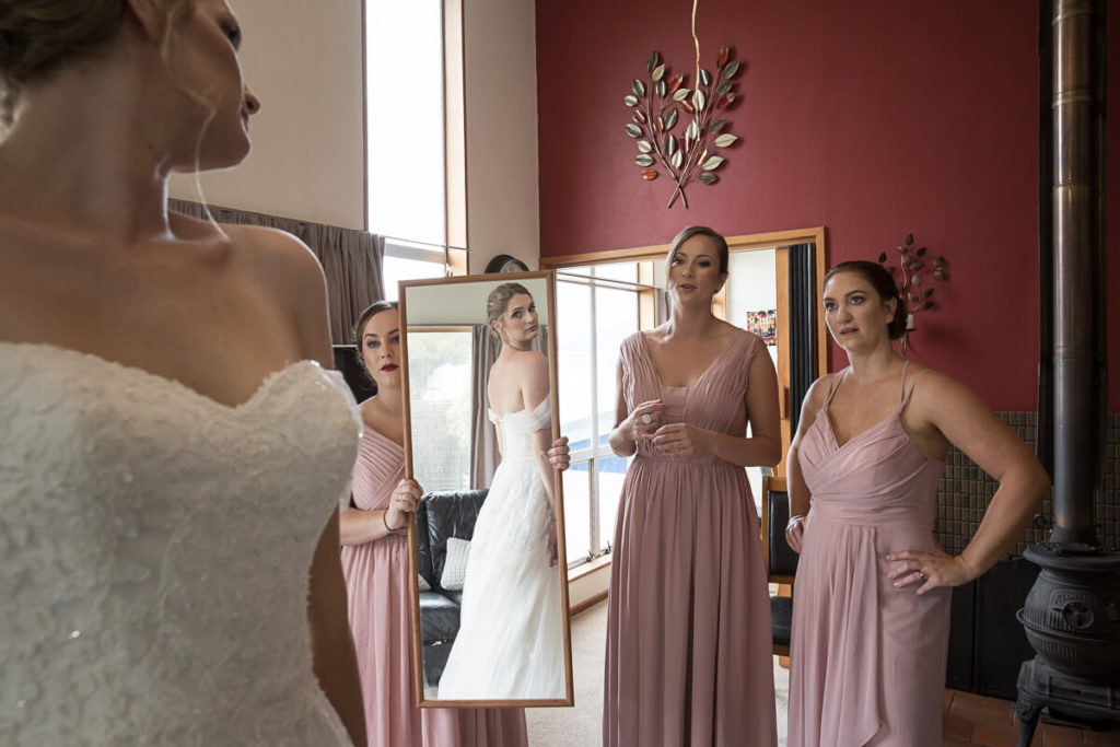 bride looking at her wedding dress in the mirror with her bridesmaids