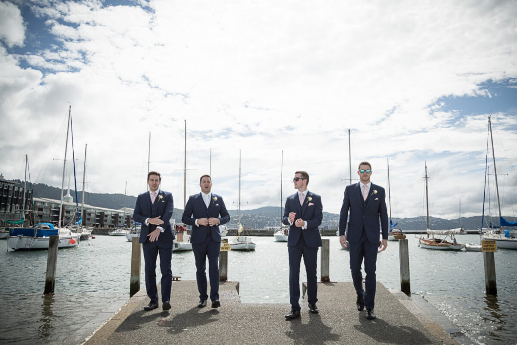 groom and grooms men walking on the jetty by wellington harbor