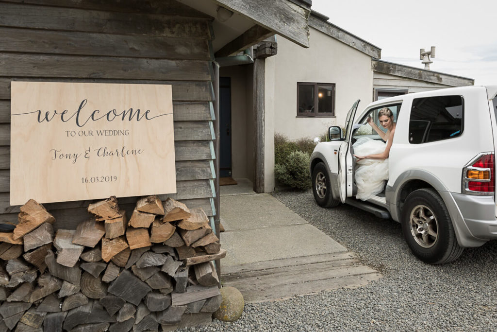 bride getting out of her wedding car and the entrance to boomrock lodge