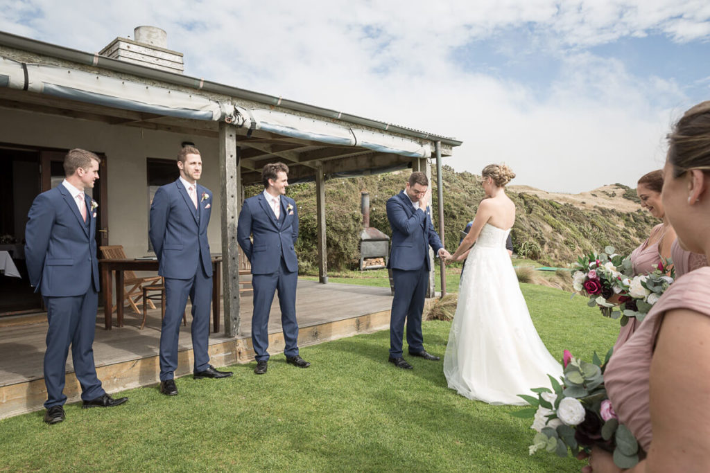 groom wiping away a tear during a wedding reception with two groomsmen int he background