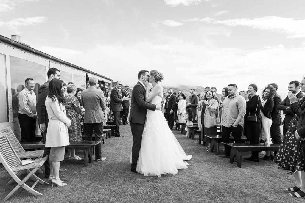 black and white image of a bride and groom sharing a kiss after walking down the isle togeather