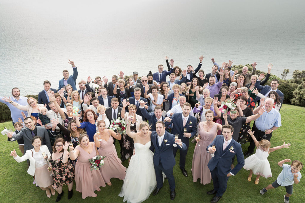 group photo of a bride and groom with all their wedding guests with the ocean in the background