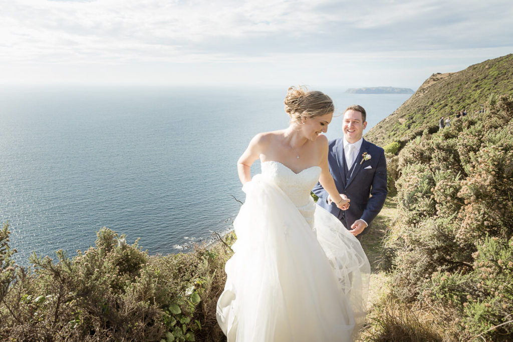 bride leading her groom along a cliff edge path at boomrock lodge with the ocean and mana island in the background