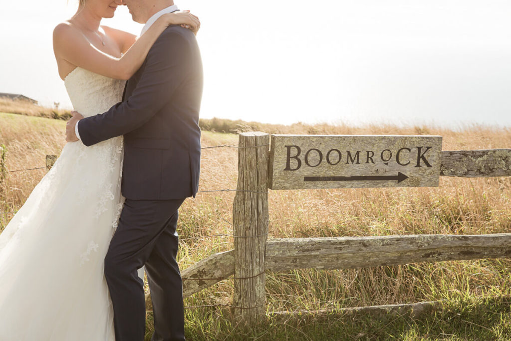 bride and groom enbracing with golden grass int he background and the boomrock sign next to them