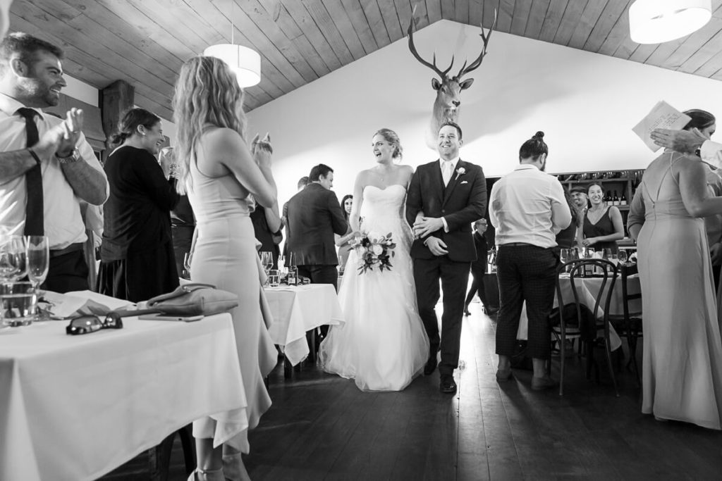 bride and groom entering thier weddign reception at boomrock lodge with all thier guests chearing in black and white