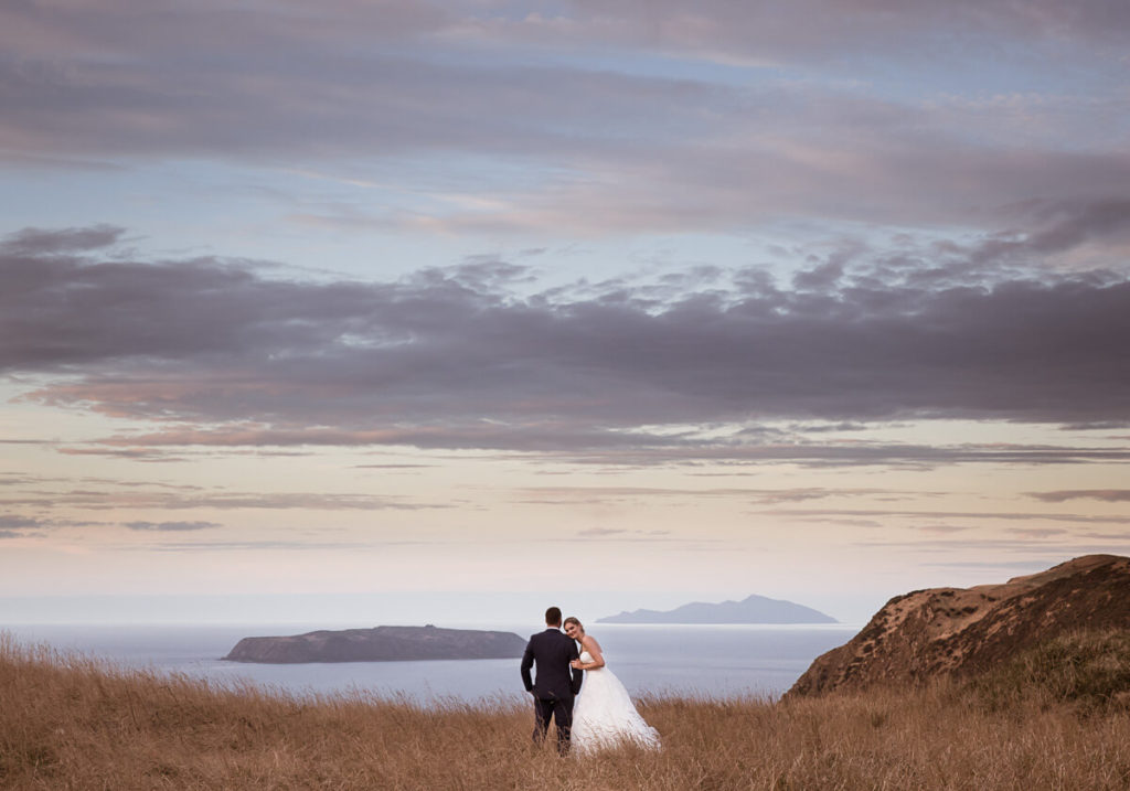 bride and groom in pink and purple sunset light in a field of golden grass and both kapiti and mana islands int eh background