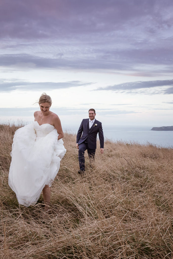 bride and groom walking though long golden grass at sunset with mana and kapiti islands in the background