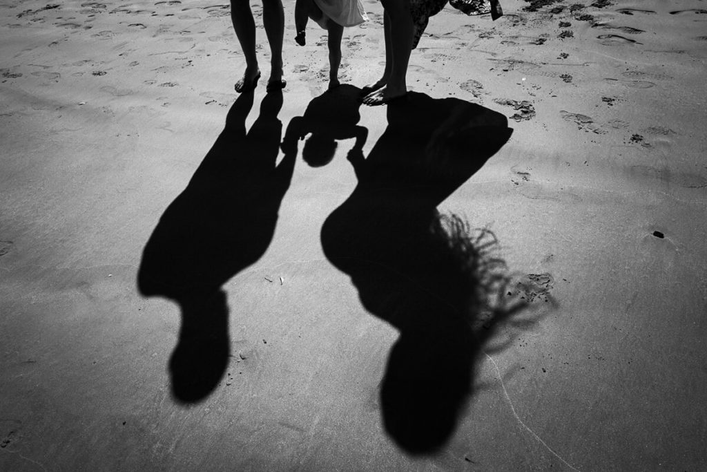shadow of pregnant mum with dad and toddler at the beach