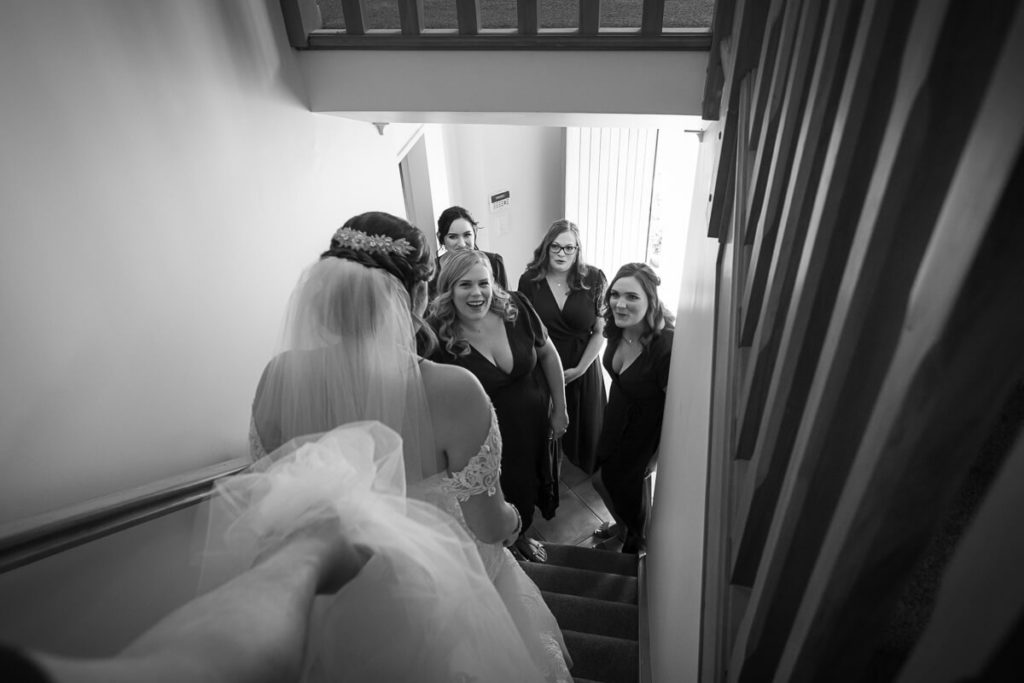 black and white image of a bride coming down stairs to be greeted by her brides maids
