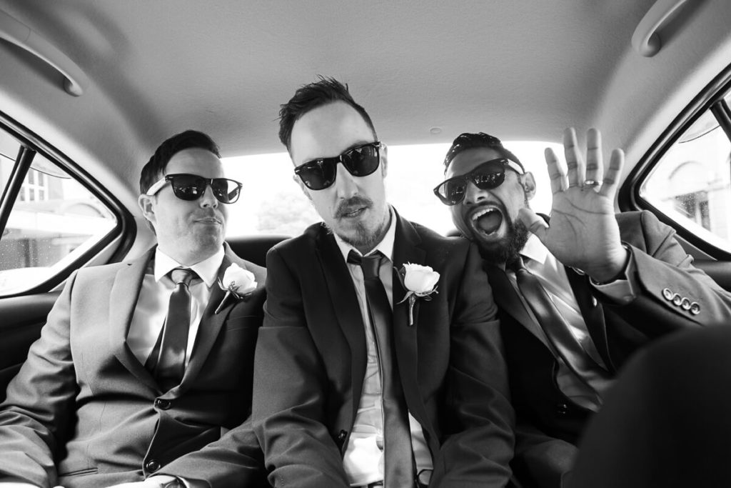 black and white image of 3 groomsmen in the back of a car