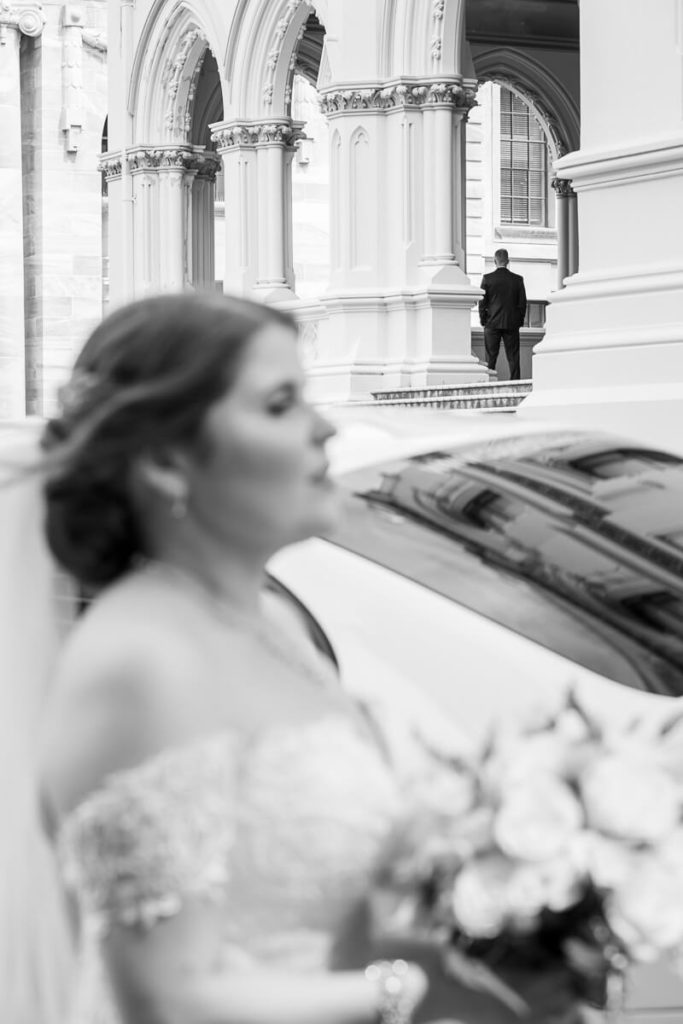 black and white image of a bride on her way to a wedding day first look with her groom waiting in the background