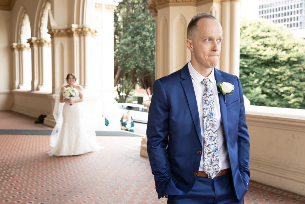 a groom waits for the first look of his bride at parliament grounds wellington