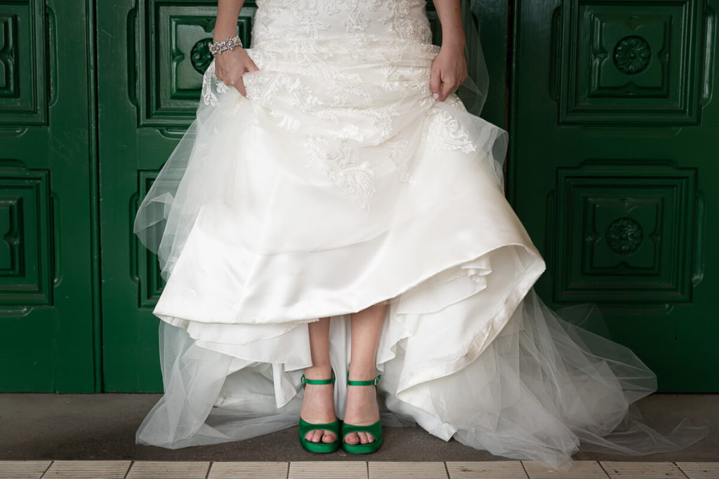 green wedding shows under a triditional white wedidng dress in front of a green door