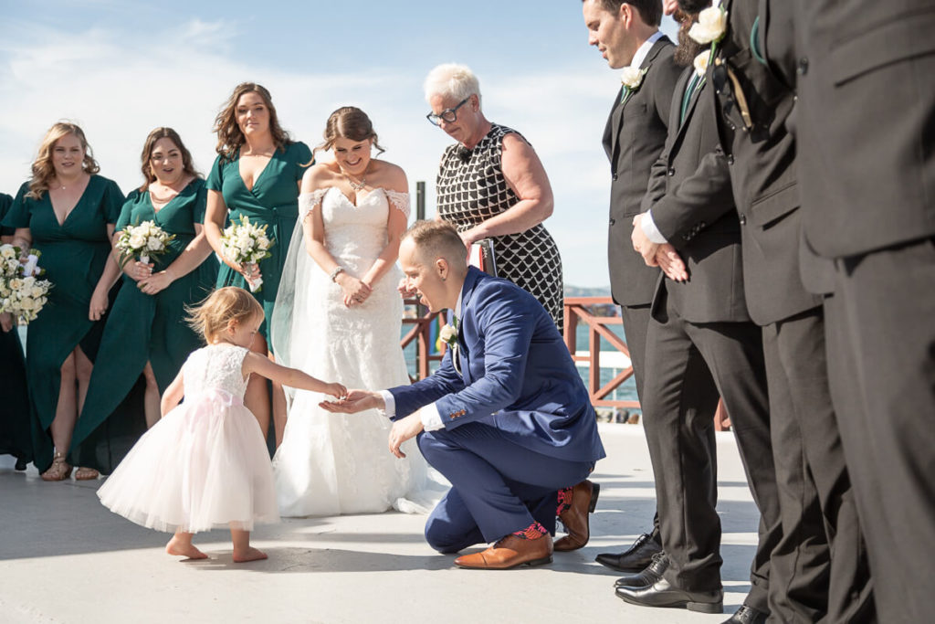 a flower-girl hands the groom the rings during a wedding ceremony