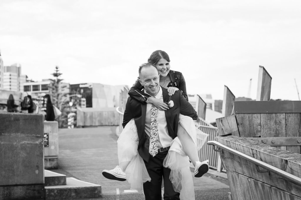 black and white wedding image of a bride in a wedding dress and leather jacket being given a piggyback ride by her groom