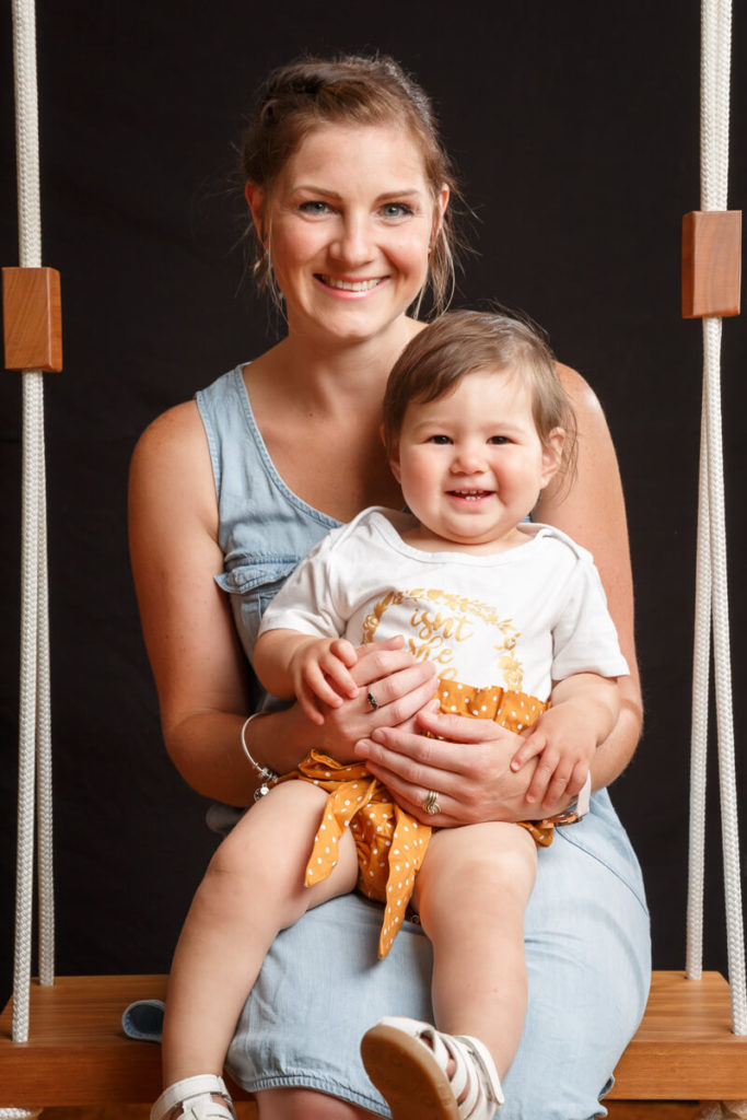 mother and one year old daughter sitting on swing in stdio with back backround