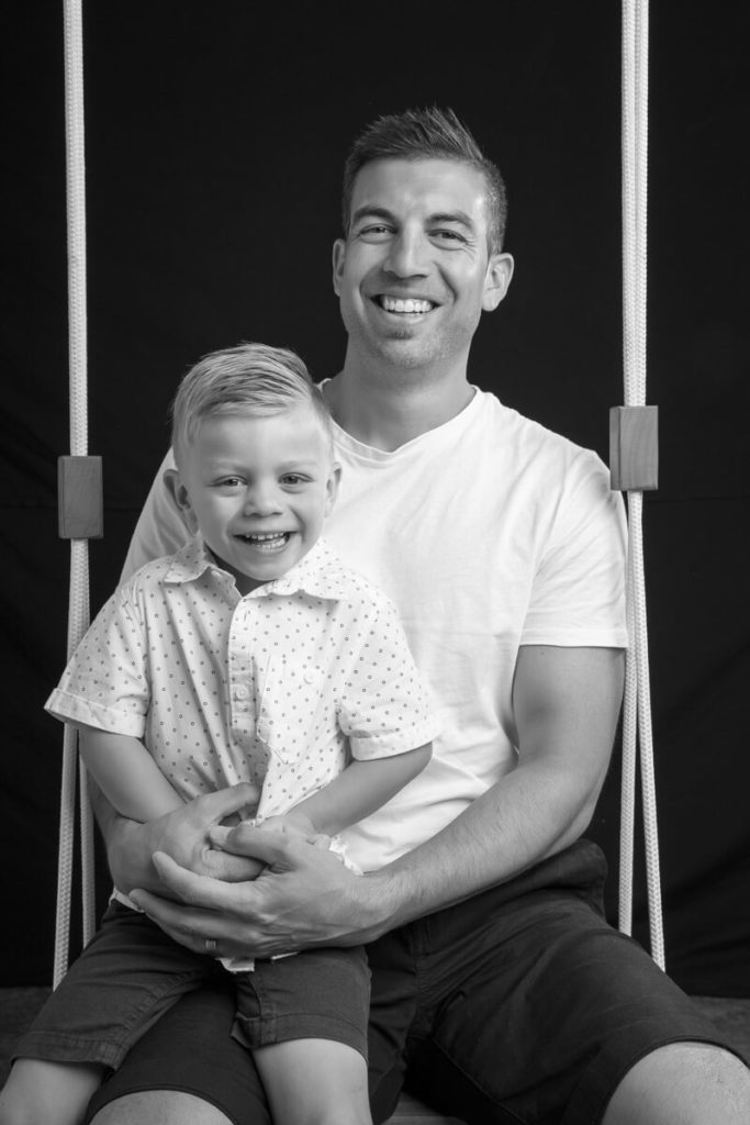 black and whit eimage of father and 3 year old son sitting on a swing with a back background