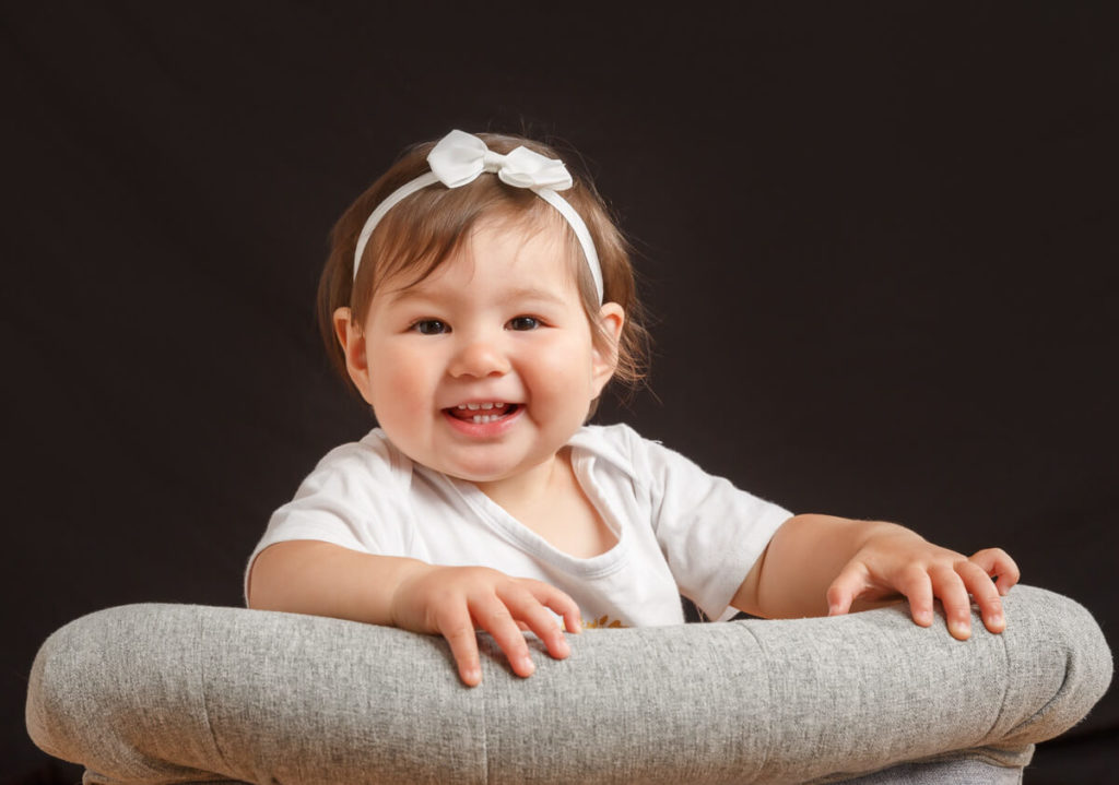 one year old girl with a white bow in her hair sitting backwards on a gray chair with a back background