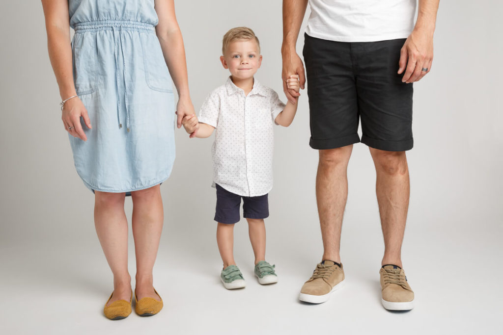 three year old my between his parents hold hands on white studio background