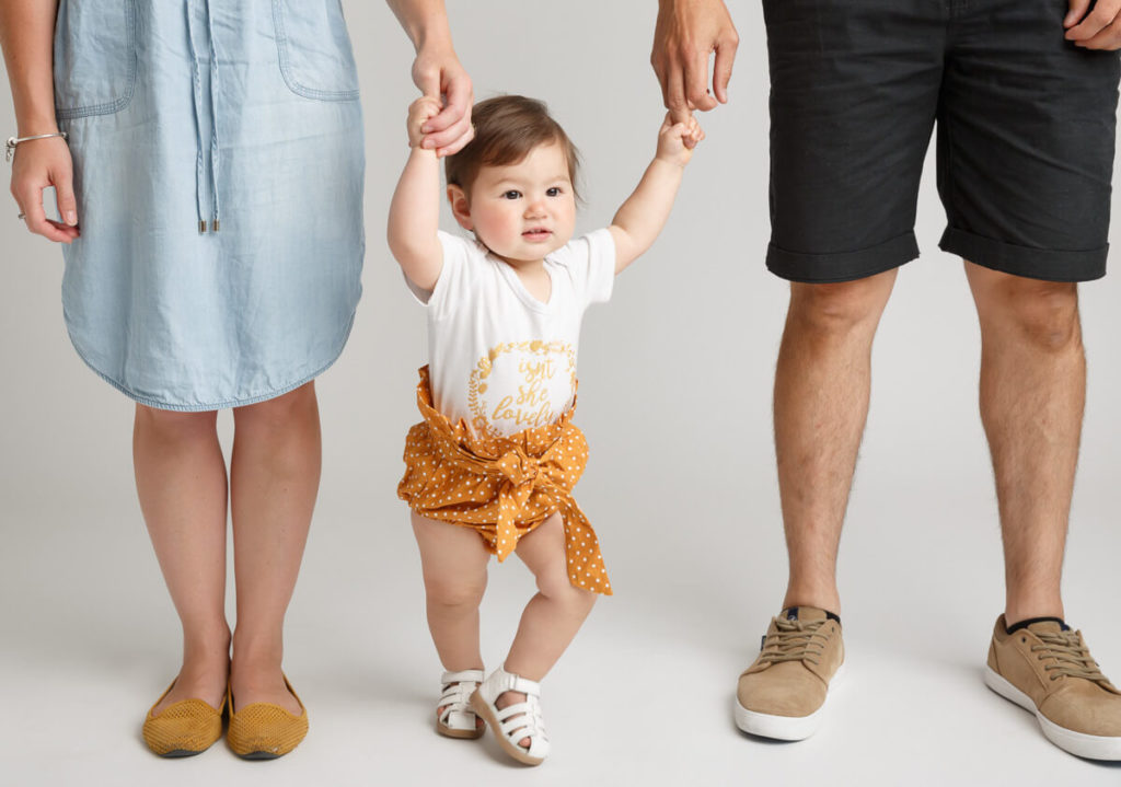 one year old girl handling hands and stanfing between her parents legs