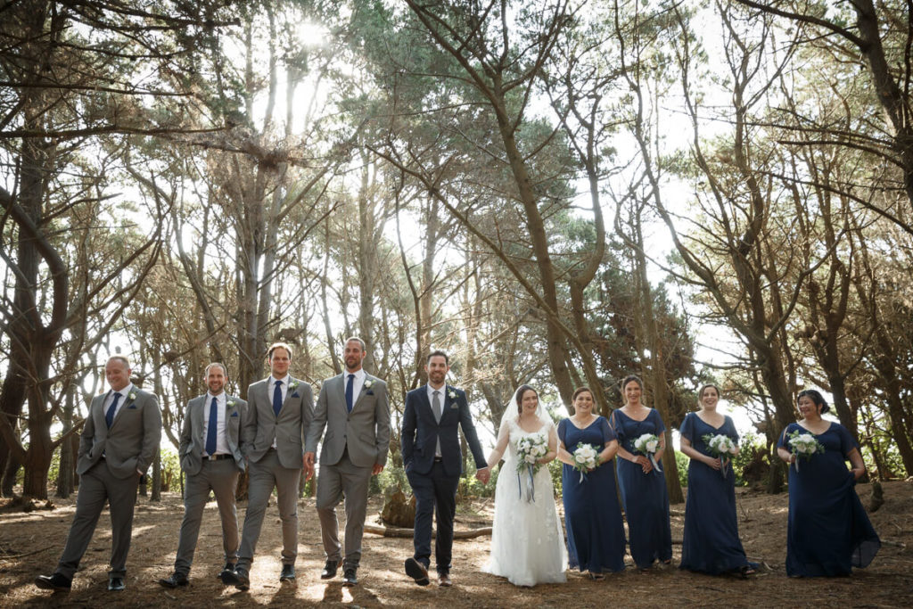 large wedding party in pine forest with sun flare
