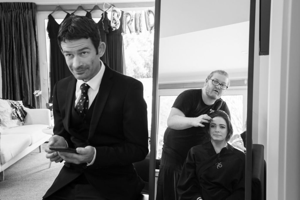 blacka nd white image of bride talking to her brother while getting ehr hair styled