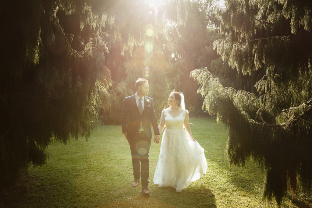 bride and groom walking togeatehr in late afternoon ligt at anam cara gardens