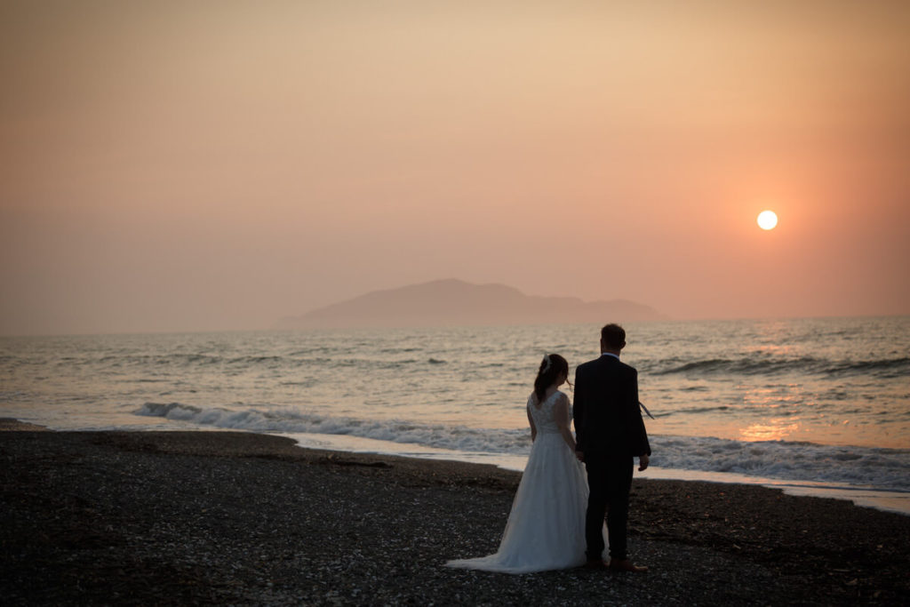 bride and groom at sunset on otaki beach with kapiti island in background