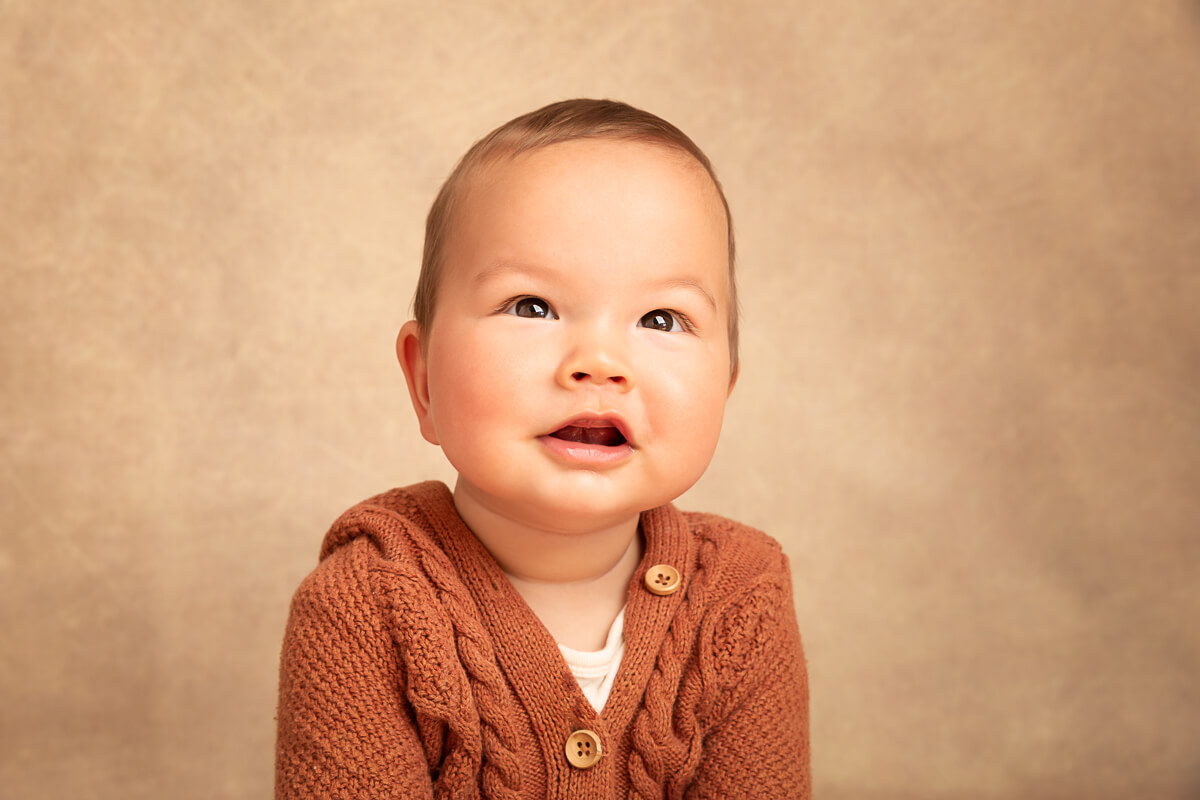 head and shoulders studio sitter session photo of a 6 month old by ina n orange knit top on a cream background