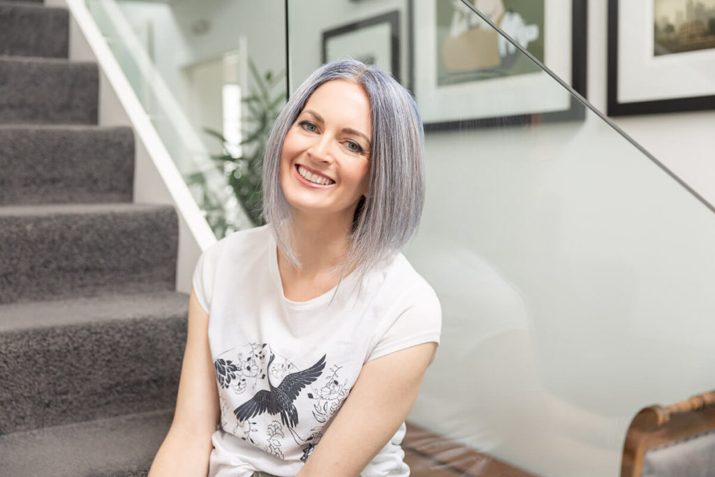 business branding photography of woman in a relaxed style sitting on some stairs smiling at the camera