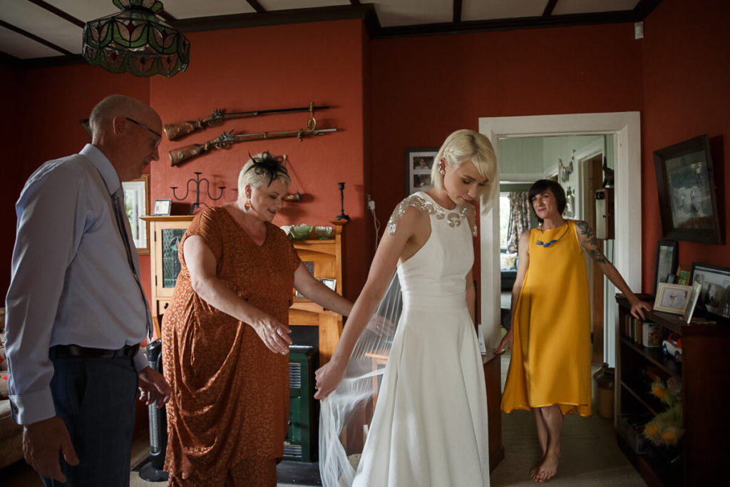 Bride showing off her DIY wedding dress and vail to her parents and bridesmaid