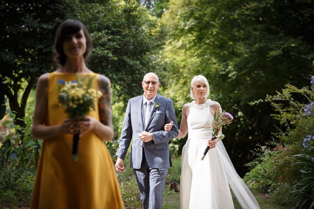 bride and bridesmaid walking down the isle in thier DIY dresses and bouquets at beautiful plamerston north garden