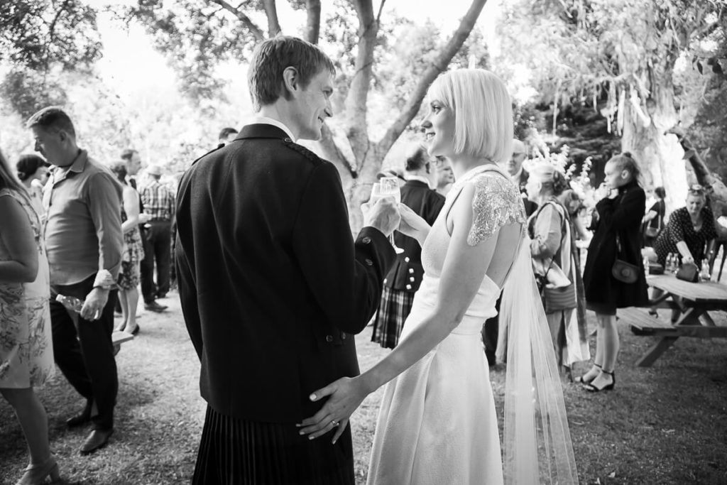 black and white photo of bride and groom celebrating their DIY wedding in plamertson north garden setting