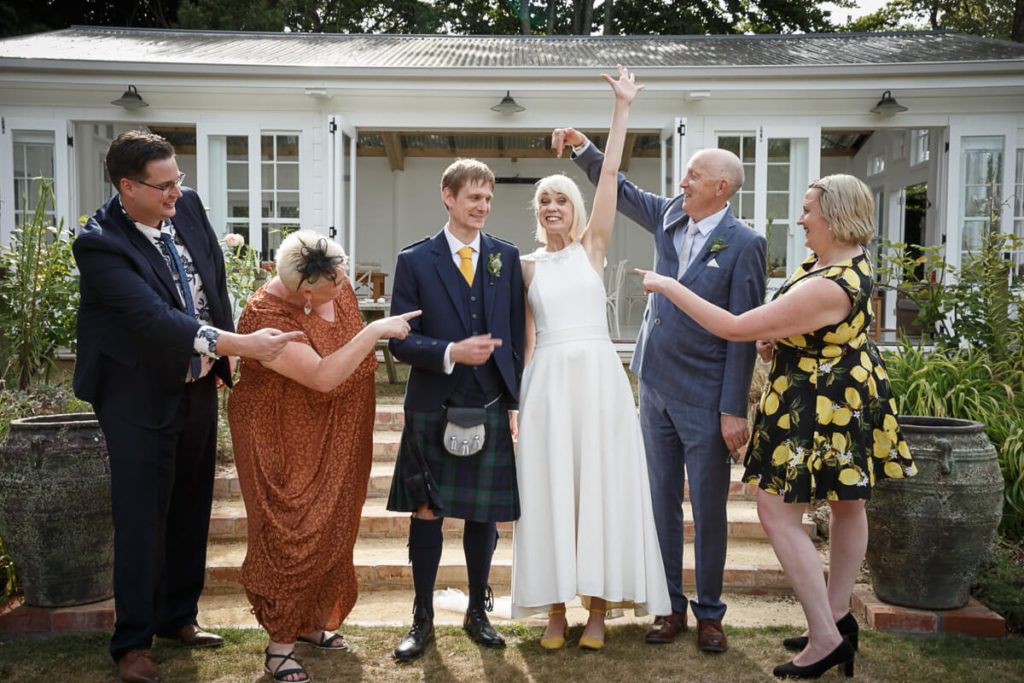Fun wedding day family photo withh brides family all pointing at her and laughing