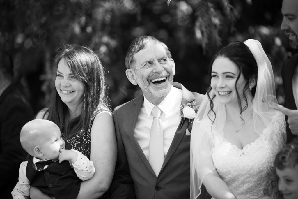 fun wedding day family photo with father of the bride laughing at anam cara gardens in black and white