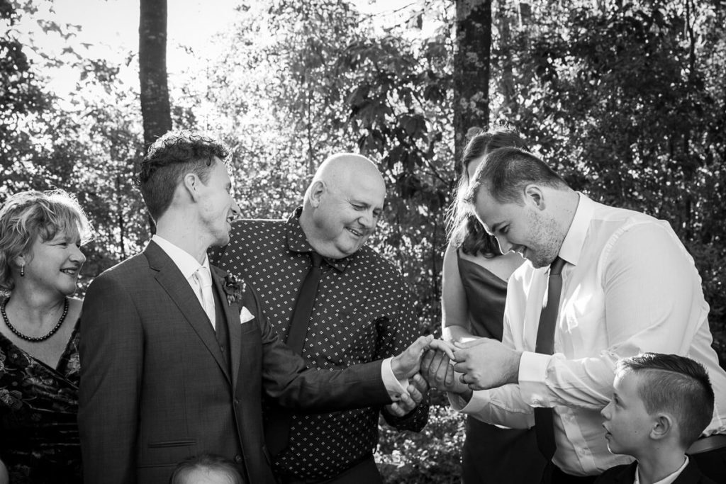 wedding day family photo of grooms family all okking at his wedding ring in black and white