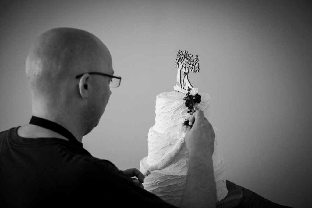 black and white photo of groom putting the final touches on the wedding cake her made for his daytime wedding