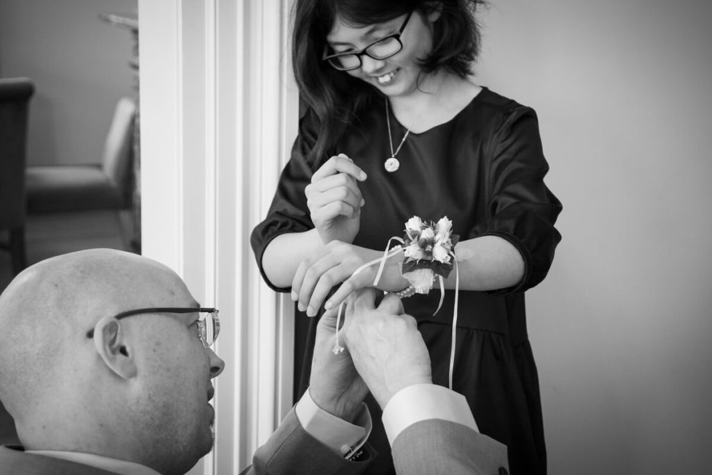 black and white image of groom helping the flowergirl with her flowers
