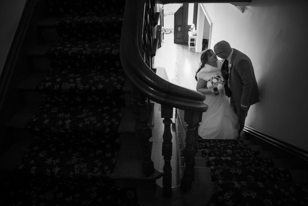 black and white image if a bride and groom kidding on the stairs at gear homestead during a dyatime wedding