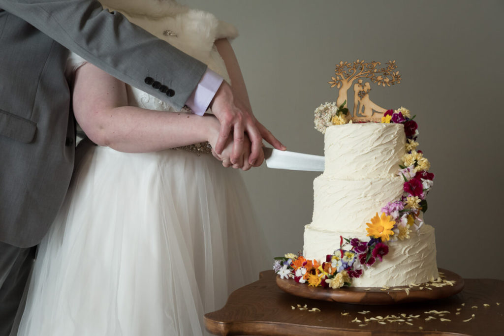 close up of bride and groom cutting thier cake during a daytime wedding at gear homestead